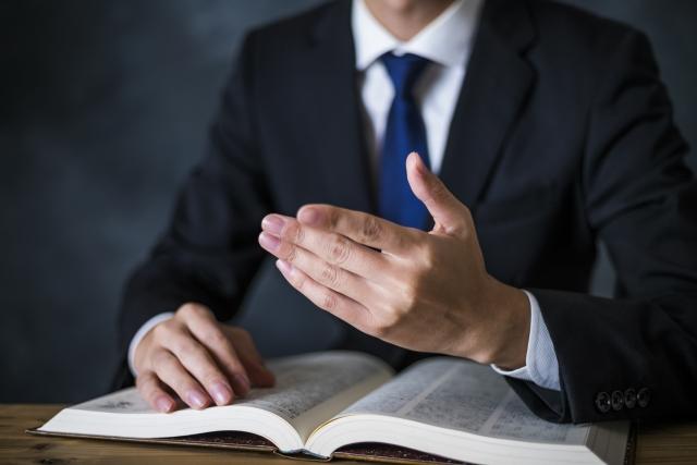 専門書を開きながら話すスーツ姿の男性の手元