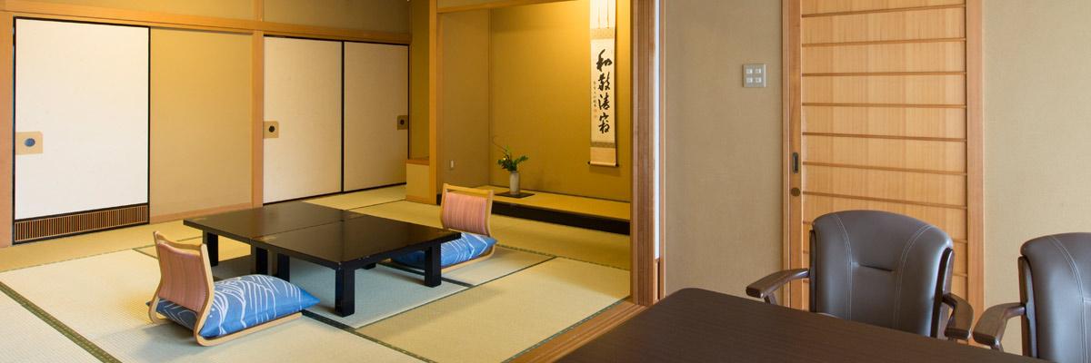 手前にテーブルセット。奥に和室と座卓。床の間には掛け軸と生け花。