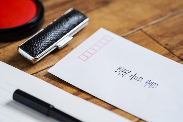 遺言書と書いた封筒と印鑑、便箋とペンが乗った木の机。