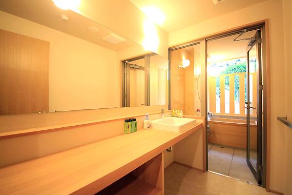 客室内の洗面所と風呂の様子。敷居には段差なし。