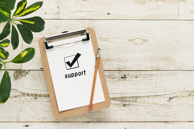 「support」と書かれたメモをはさんだクリップボードとペン。