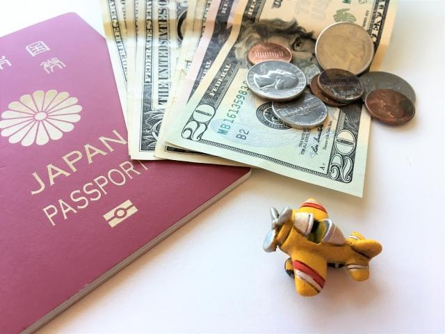 海外の紙幣・コインとパスポート、ミニチュアの飛行機