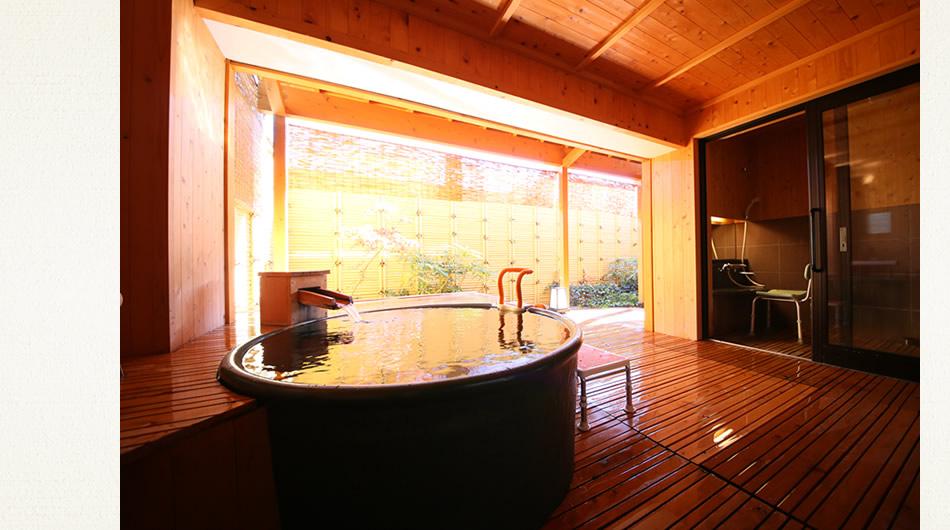 客室風呂の様子。源泉かけ流しと手すり。奥のシャワールームには介助用シャワーチェア