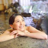温泉に入り微笑む女性