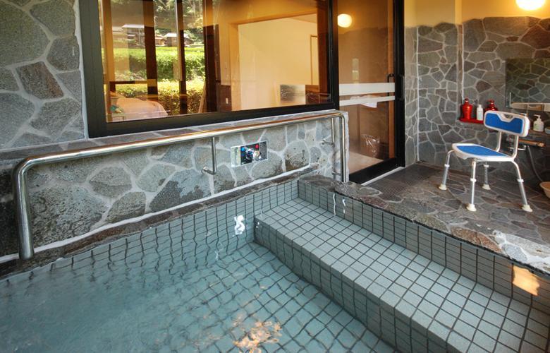 客室内半露天風呂。手すりとシャワーチェアがある。