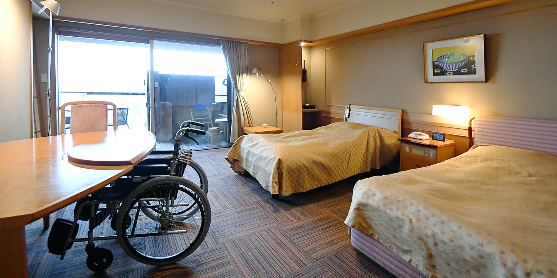 右にリクライニングベッド2台。左にテーブルと車椅子。奥には露天風呂。