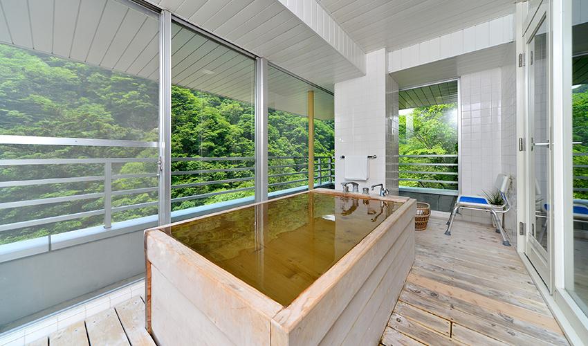 客室内の檜展望風呂の様子。奥に介助用シャワーチェア。