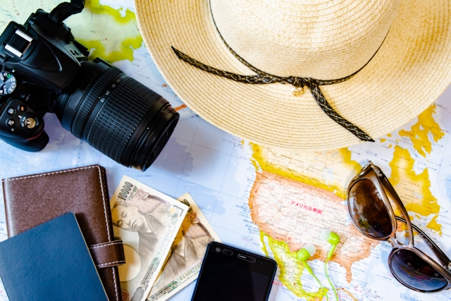広げた世界地図の上に麦わら帽子・一眼レフカメラ・サングラス・パスポート・財布・紙幣・スマートホンを置いている