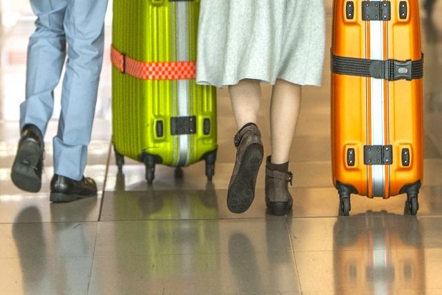 スーツケースを引いて歩いていく男女の脚元