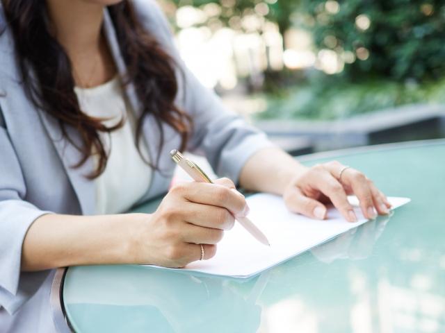 書類に書き込む女性。晴れた屋外のテーブルにて。