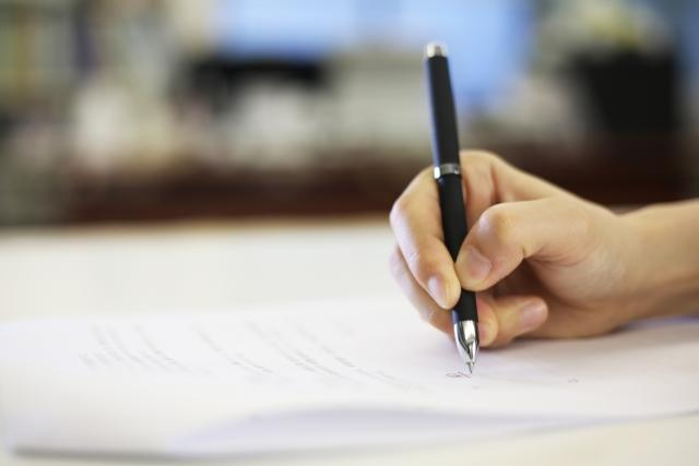 紙にペンで文字を書く右手