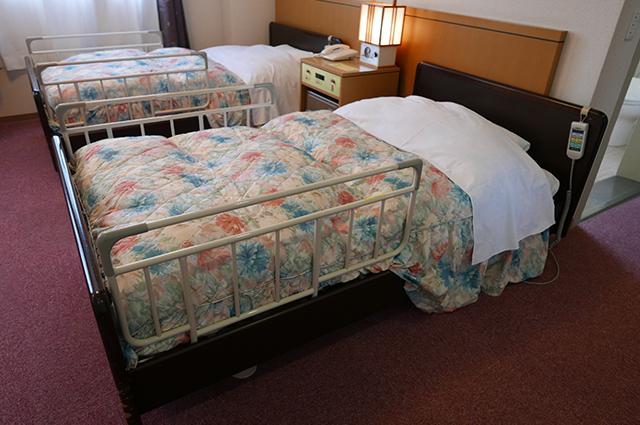 リクライニングベッドが2台並んでいる。間にサイドテーブルがある。