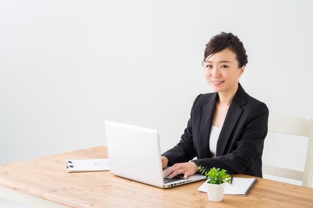 パソコンの前でほほえむ女性