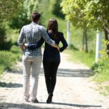 肩を組み木々の中の道を散歩する夫婦の後ろ姿