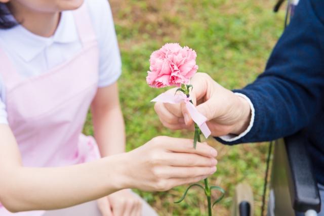 介護者に花を渡す