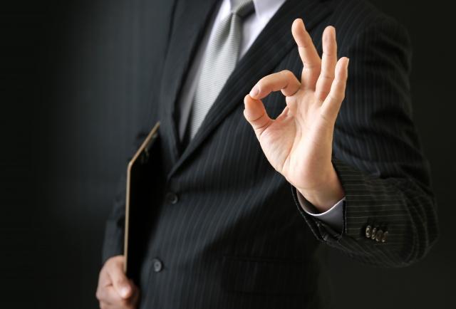 指でOKマークを作るビジネスマン