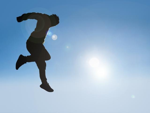 青空にジャンプする青年