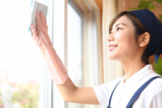 窓拭きをするハウスキーパー(家政婦)の女性