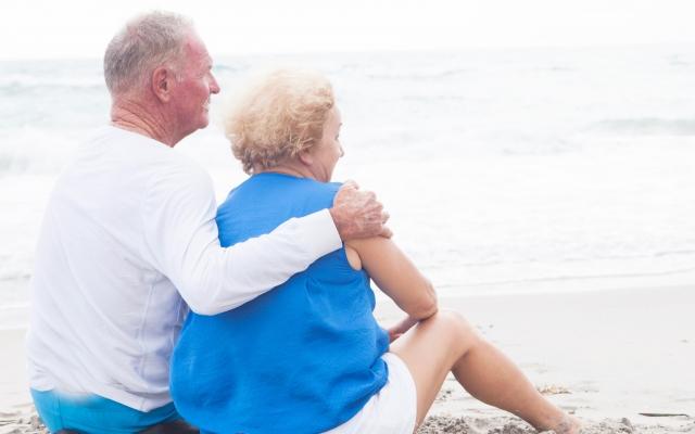 砂浜に座る外国人老夫婦